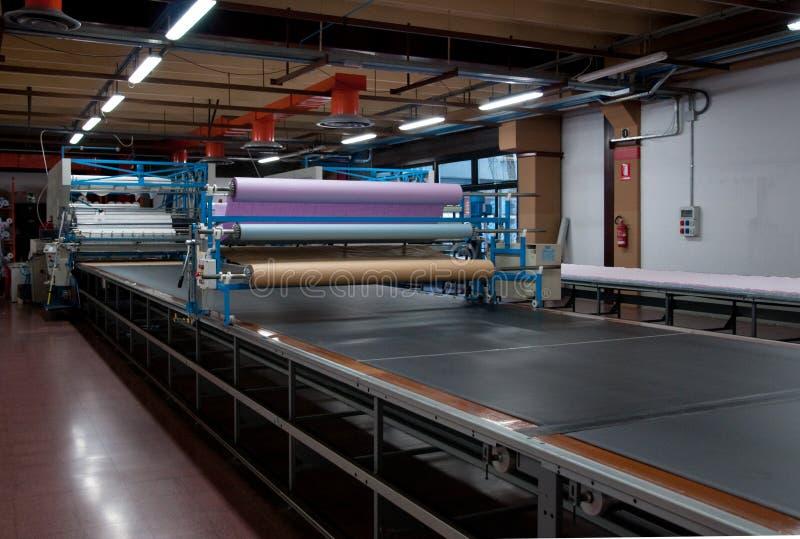 自动地给穿衣的剪切工厂纺织品 库存照片