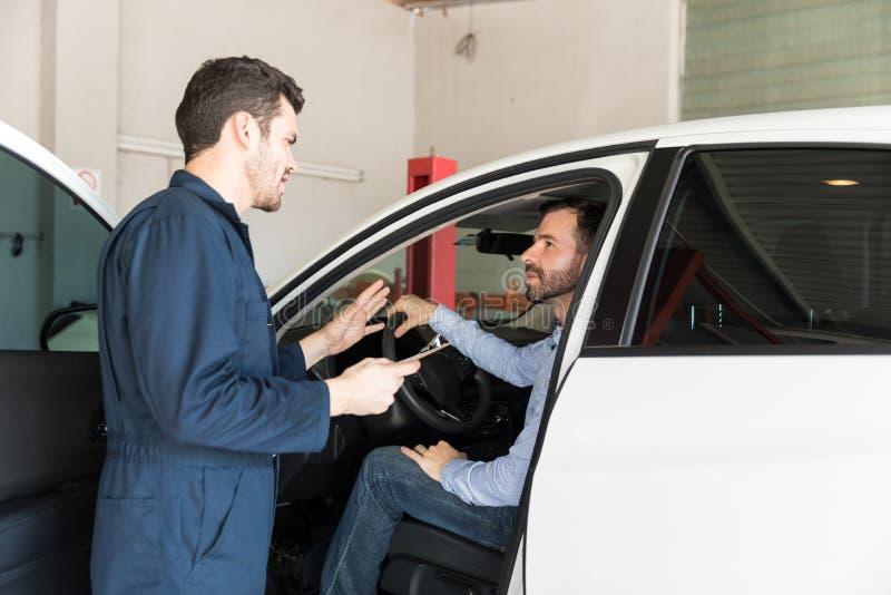 自动安装工谈论与顾客在汽车在车库 免版税库存照片
