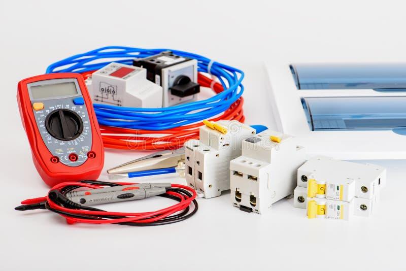自动开关、配电盒、缆绳和数字式多用电表在白色背景 电机设备 免版税图库摄影
