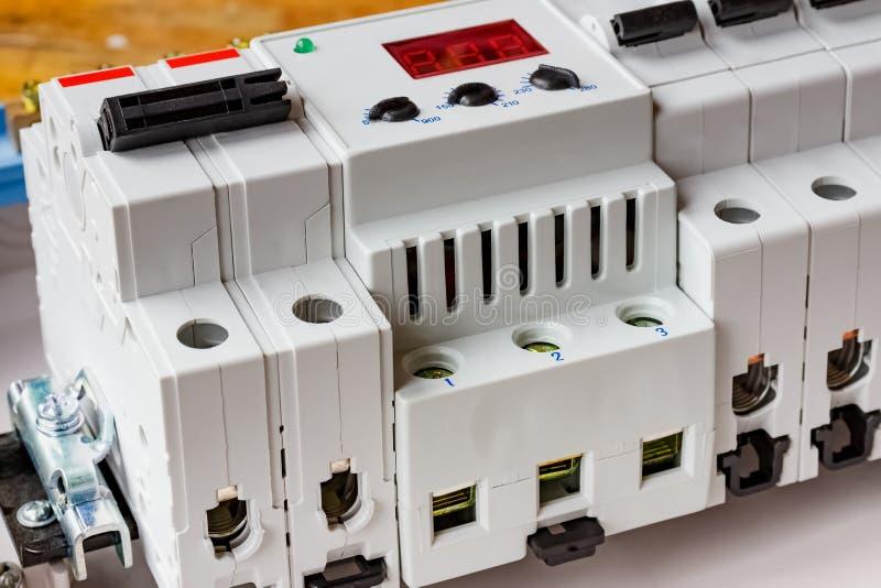 自动开关和在DIN路轨安装的电压防幅器在白色塑料登上的箱子特写镜头 免版税图库摄影