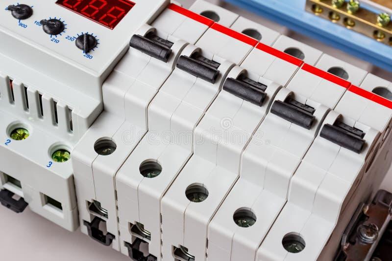 自动开关和电压防幅器在DIN路轨在白色塑料登上的箱子 免版税库存照片
