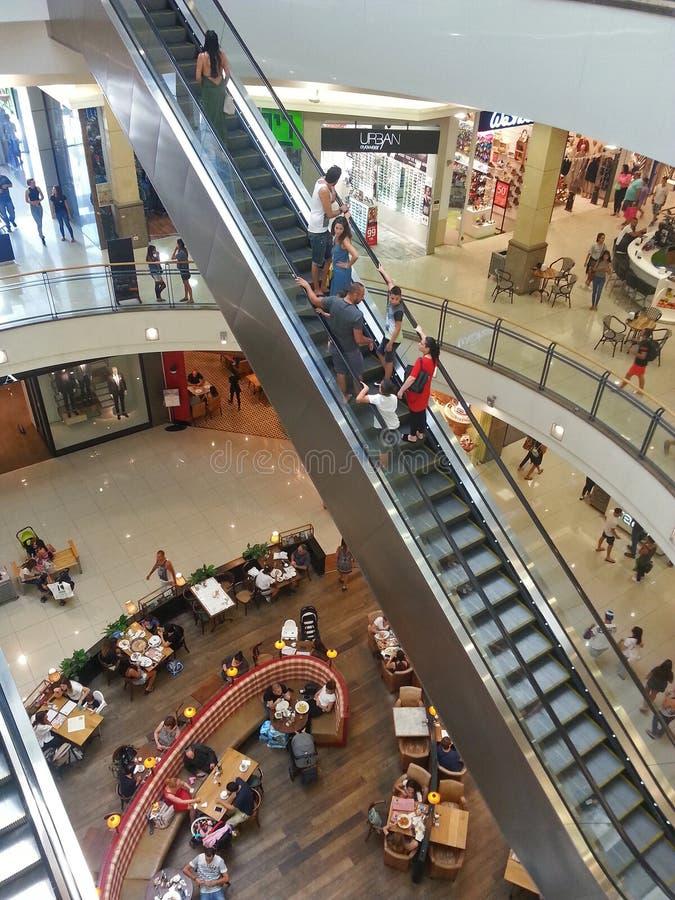 自动扶梯的人们和走在购物购物中心销售, consu 免版税库存照片