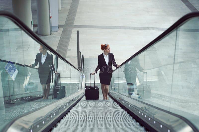 自动扶梯的女实业家与手提行李 免版税库存图片