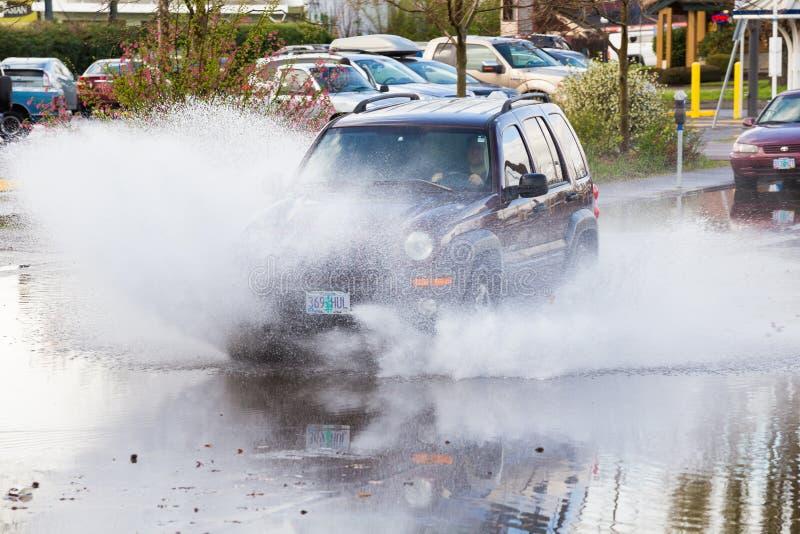 自动驾驶在水坑在大雨以后 免版税库存图片