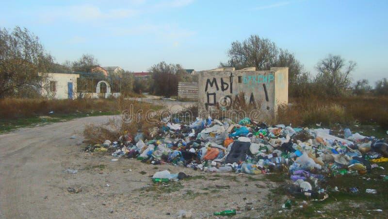 自发倾销在住宅房子附近的家庭垃圾 免版税图库摄影