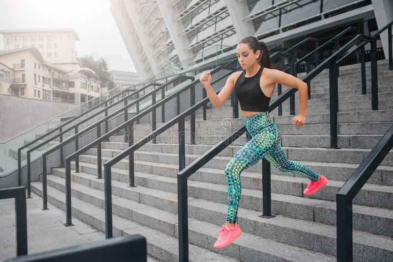 自发和被集中的年轻女人跑她非常快速地做它在步 下来式样神色 她佩带美丽 免版税图库摄影