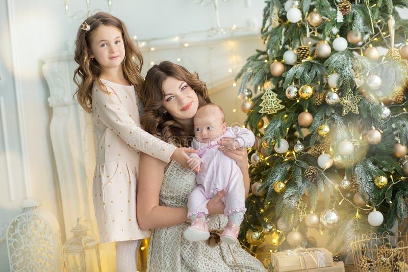 自圣诞前夕的家庭在壁炉 打开Xmas礼物的孩子 孩子在与礼物盒的圣诞树下 装饰的生活 库存图片
