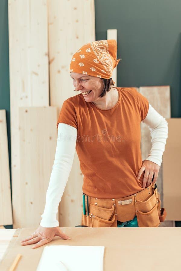 自己经营的女性木匠微笑的画象 免版税库存照片