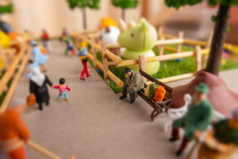 自已修建了微型玩具概念人在动物园-长凳的无家可归的人,学校孩子,坐的老人  库存照片