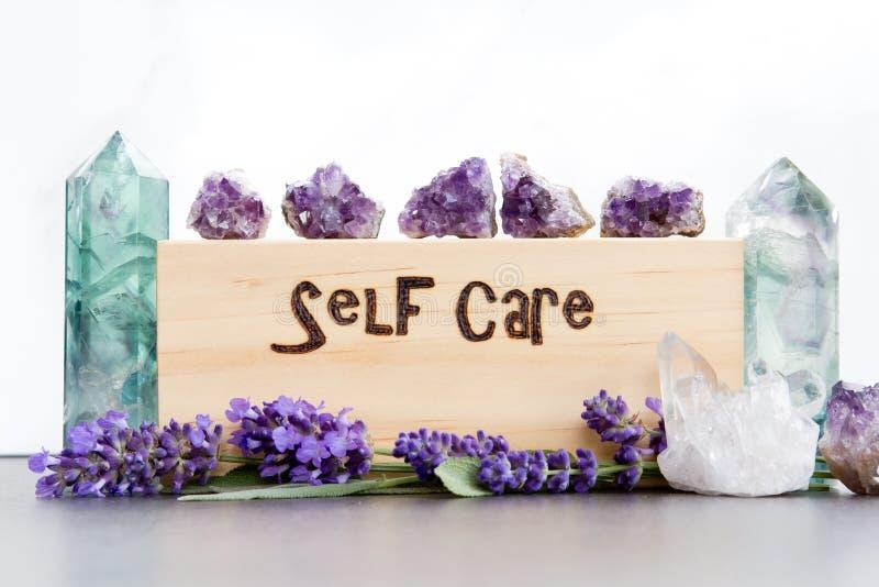 自已关心-在与紫色淡紫色花、紫晶、荧石和水晶的木头烧的词在板岩有白色背景 库存照片