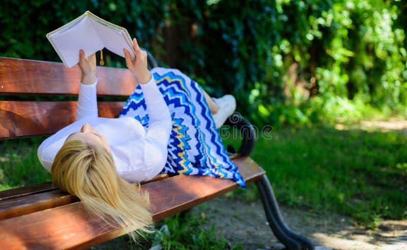 自我改善的时刻 妇女花费与书的休闲 夫人喜欢读 读的女孩户外,当放松时 免版税图库摄影