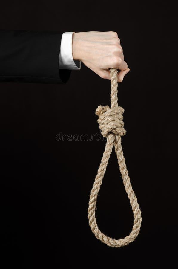 自杀和企业题目:一个商人的手在拿着绳索的圈垂悬的一件黑夹克的在黑色被隔绝 免版税库存照片