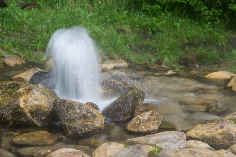 自流井 春天,自然环境的爆发 石头和水 喷发出于地面的干净的饮用的地水 库存照片