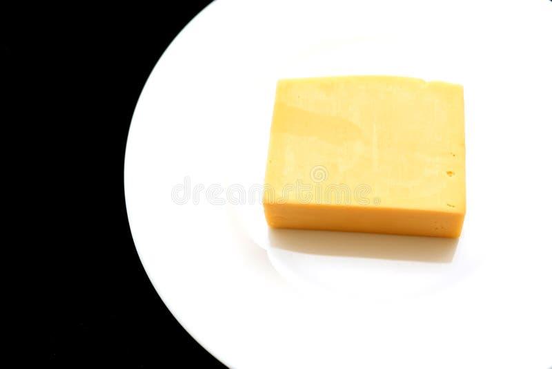 乳酪片断的特写镜头在一块白色板材的在黑背景 自然乳制品,好吃 免版税库存照片