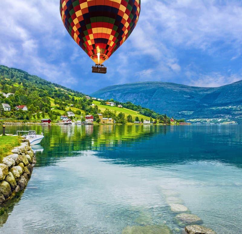 自然农村风景 镇和巡航在挪威海湾端起从前,热空气气球 免版税库存图片