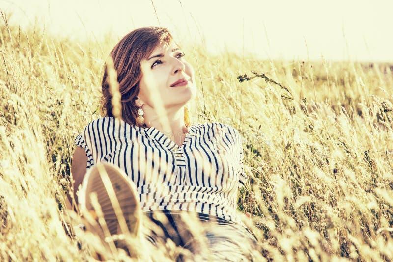 自然可爱的妇女摆在夏天草甸的,黄色照片f 免版税库存图片