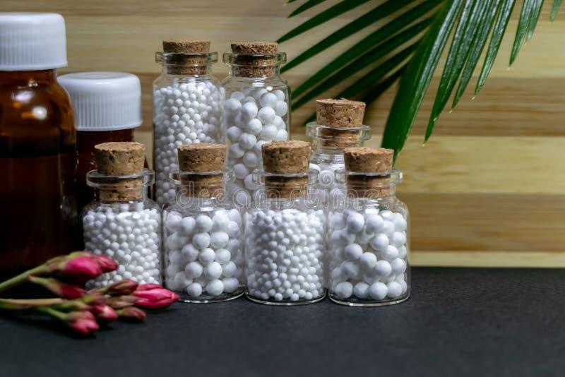 自然同种疗法概念–包括药片的同种疗法药物和液体物质瓶、桃红色花和绿色叶子  免版税图库摄影