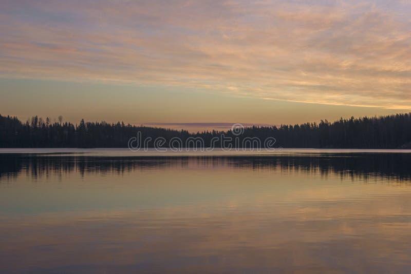 自然在湖的晚上日落 在水反映的美丽的树 免版税库存照片