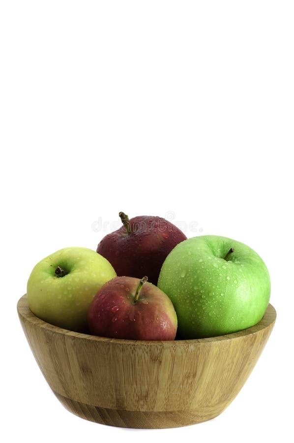 自然在白色背景隔绝的一个木碗的颜色红色,绿色和黄色苹果 库存照片