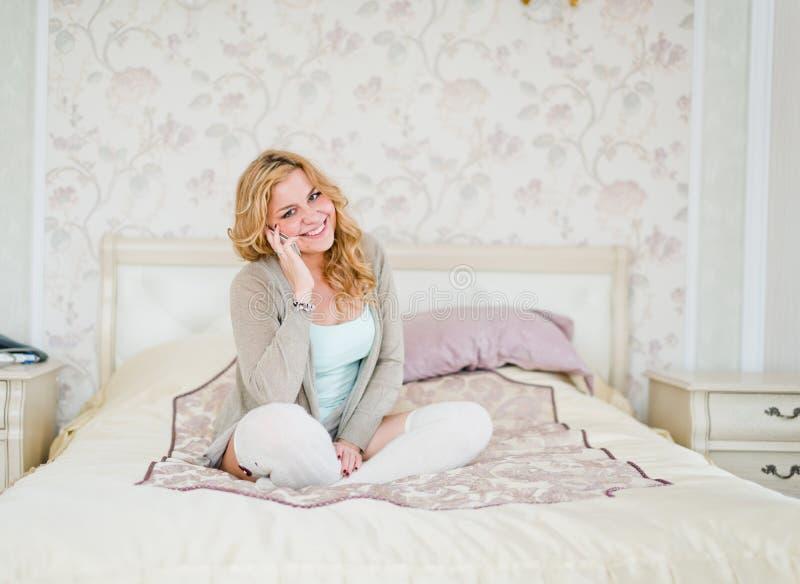 自然快乐白肤金发说谎在床上和打电话在明亮的bedro 库存照片