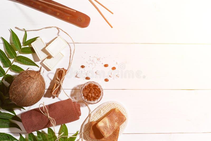 自然手工制造肥皂用咖啡豆、桂香、海盐、丝瓜络、棕色毛巾、椰子和绿色叶子在白色 免版税图库摄影