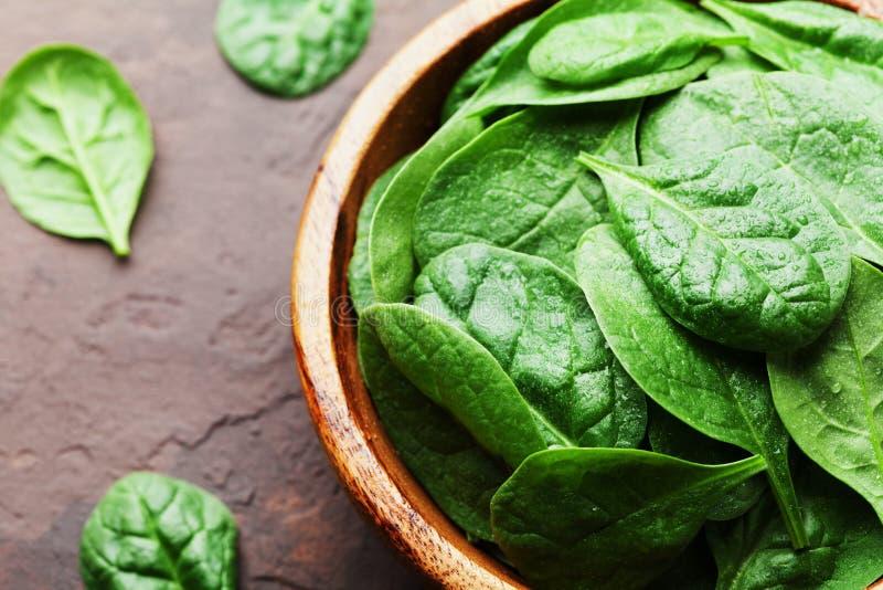 自然新鲜的婴孩菠菜在木碗离开在葡萄酒石头桌 有机健康食物 免版税库存照片