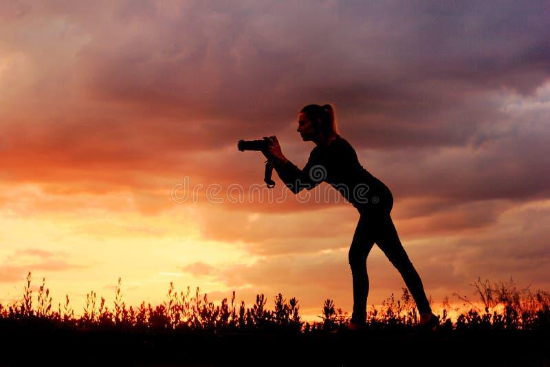 自然旅行摄影师妇女剪影 免版税库存图片