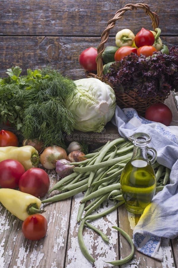 自然有机新鲜蔬菜,蕃茄富有的收获,绿叶,橄榄油,在木背景的青豆 免版税图库摄影