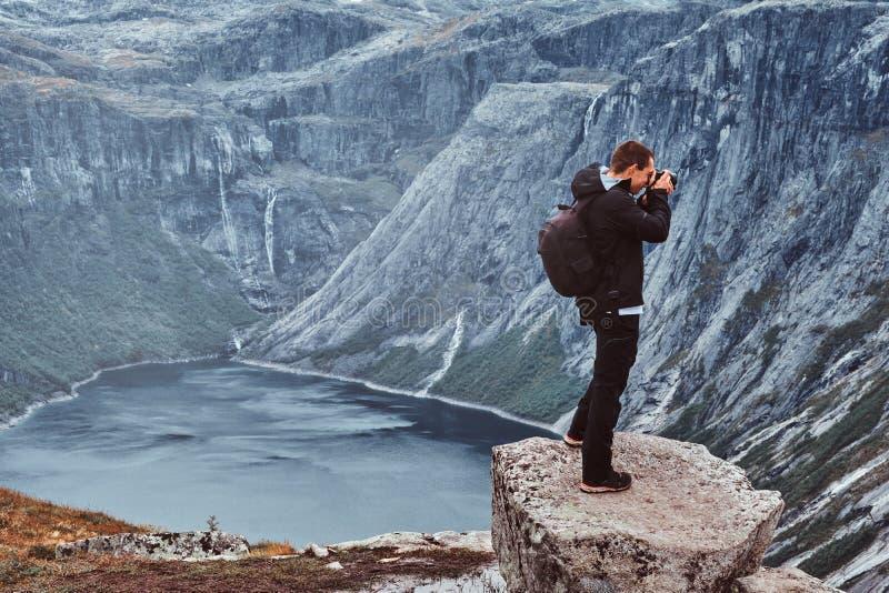 自然有照相机射击的摄影师游人,当站立在挪威山时 库存照片