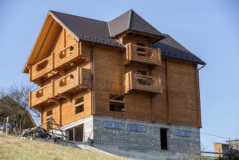 自然木材材料新的木生态传统村庄房子与下木瓦屋顶和石地下室的 图库摄影