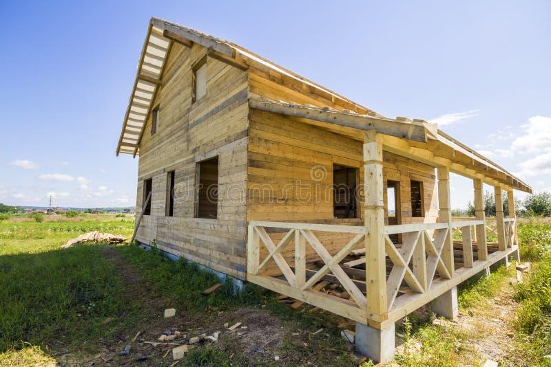 自然木材材料未完成的木生态传统村庄广角看法与下陡峭的屋顶和门廊的 图库摄影