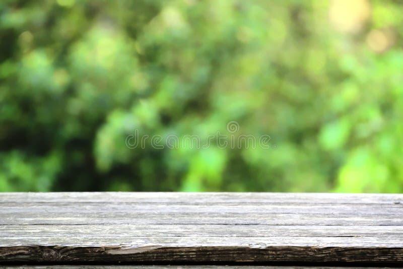 自然木桌在反对blured绿色背景的一个土气环境里 空的拷贝空间 免版税库存照片