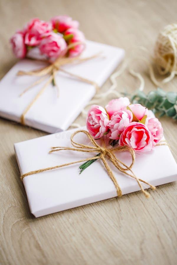 自然样式在木桌上的被手工造的礼物盒 在白皮书包裹的手工制造当前箱子 花卉装饰元素 库存照片