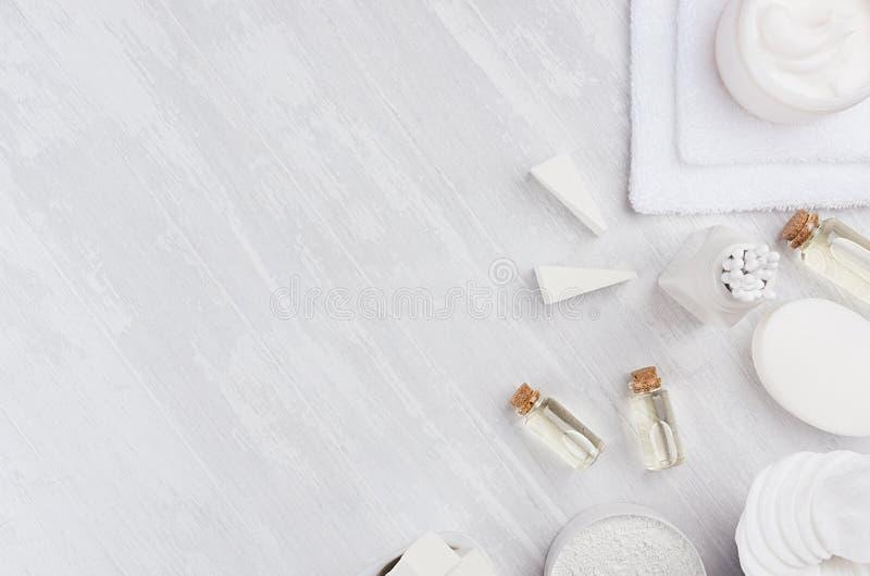 自然温泉按摩油和白色化妆用品产品,有棉花毛巾的浴辅助部件在白色木板,顶视图,边界 图库摄影