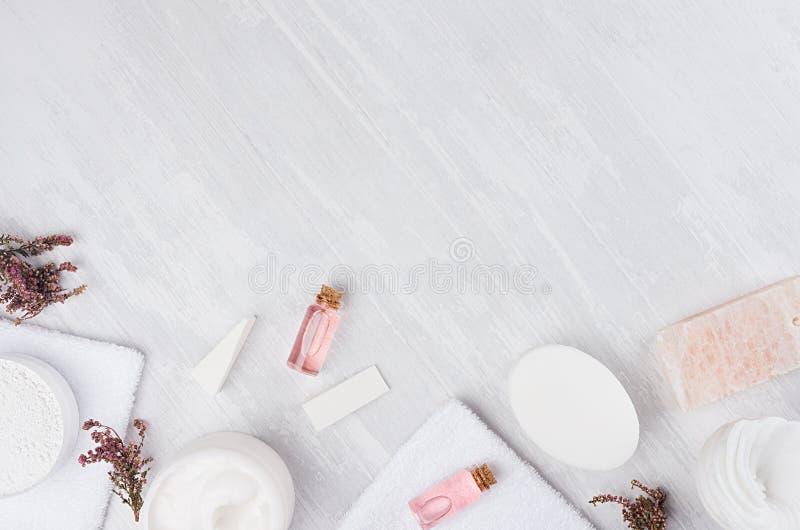 自然温泉白色和桃红色化妆用品产品和浴辅助部件有桃红色花的作为框架在白色木板,顶视图 免版税图库摄影
