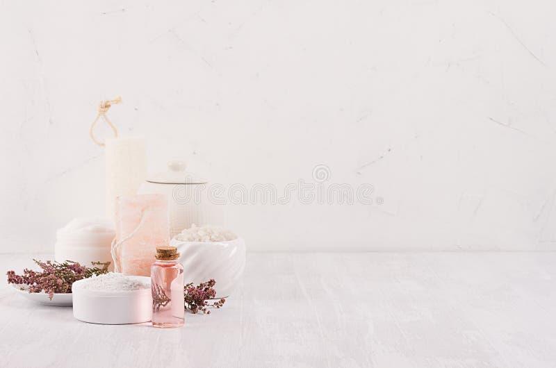自然温泉白色和桃红色化妆用品产品和浴辅助部件有桃红色花的在白木委员会,内部 免版税库存图片