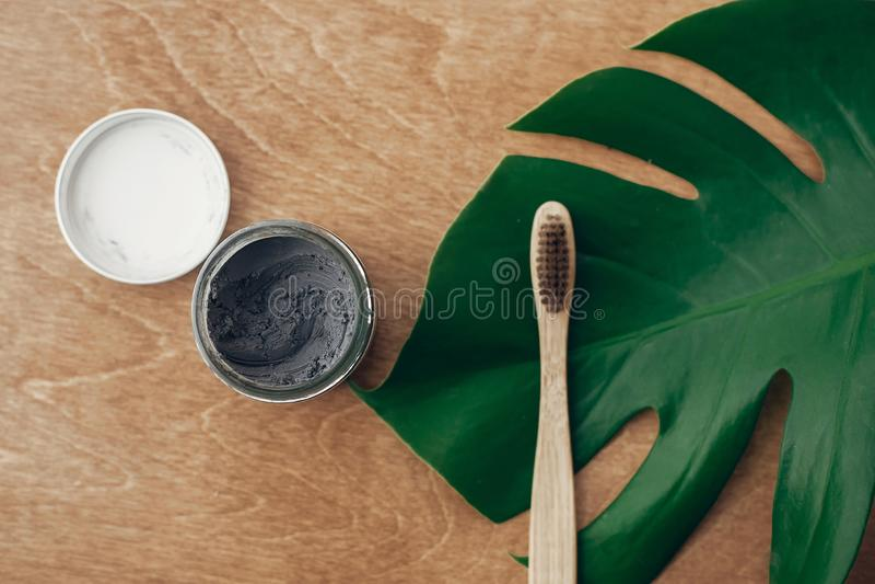 自然牙膏在玻璃瓶子和竹牙刷的活性炭在与绿色monstera叶子的木背景 塑料 免版税库存图片