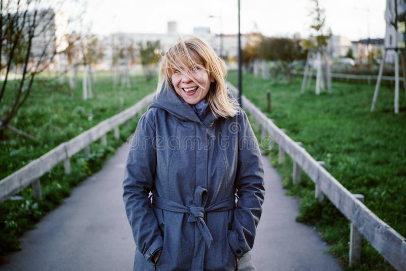 自然白肤金发的愉快的妇女身分在一个秋季公园 秋天,室外和生活方式概念 免版税库存照片
