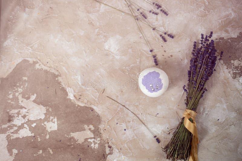 自然的化妆用品 手工制造淡紫色浴炸弹、淡紫色花和毛巾在白色木板条,顶视图 库存照片