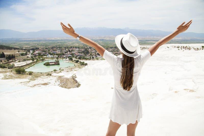 自然石灰华水池和大阳台在棉花堡 棉花城堡在土耳其西南部,白色礼服的女孩有帽子自然poo的 免版税库存图片
