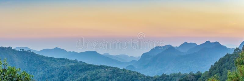 自然网横幅 山景日落全景视图许多小山和绿色森林盖子有软的薄雾的与五颜六色的天空 免版税库存图片