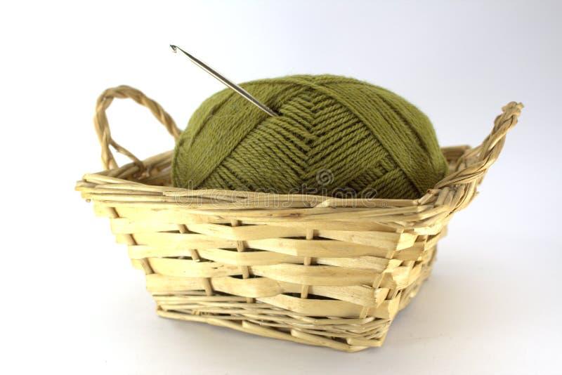 自然羊毛绿色缠结针线的与钩针编织的钩针编织在它黏附了在一个柳条筐在白色背景 免版税库存照片