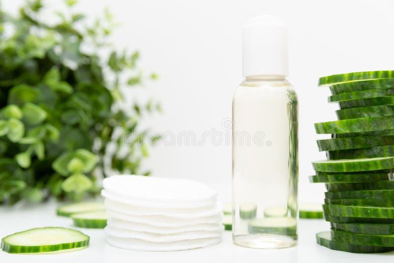 自然美人补救 在瓶,绿色黄瓜切片,早晨面部新鲜的清洁剂补品的液体skincare化妆用品 免版税库存图片