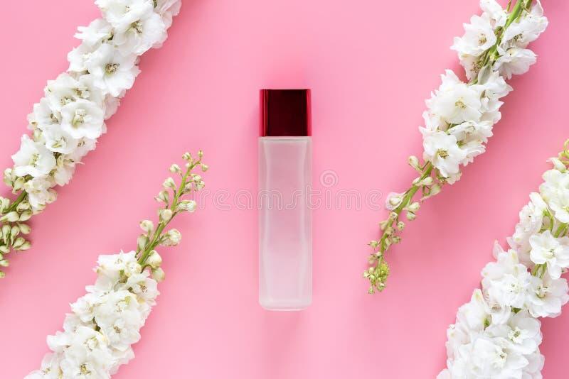 自然美人skincare产品 有白色春天花的豪华化妆瓶容器草本在粉红彩笔背景 图库摄影