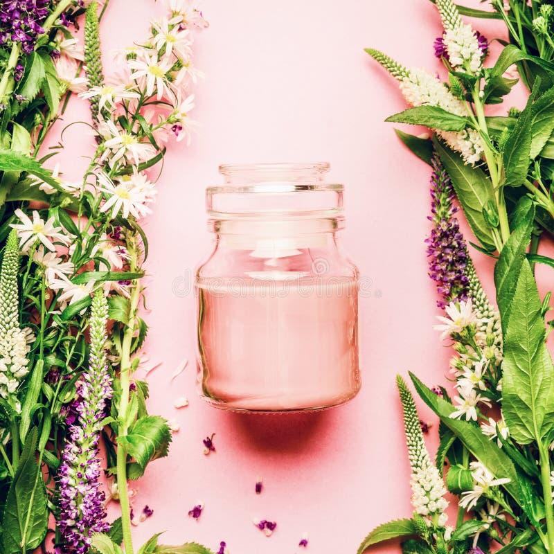 自然草本护肤化妆用品概念 玻璃瓶子用奶油色和新鲜的草本和花在桃红色背景,顶视图,拷贝温泉 库存照片