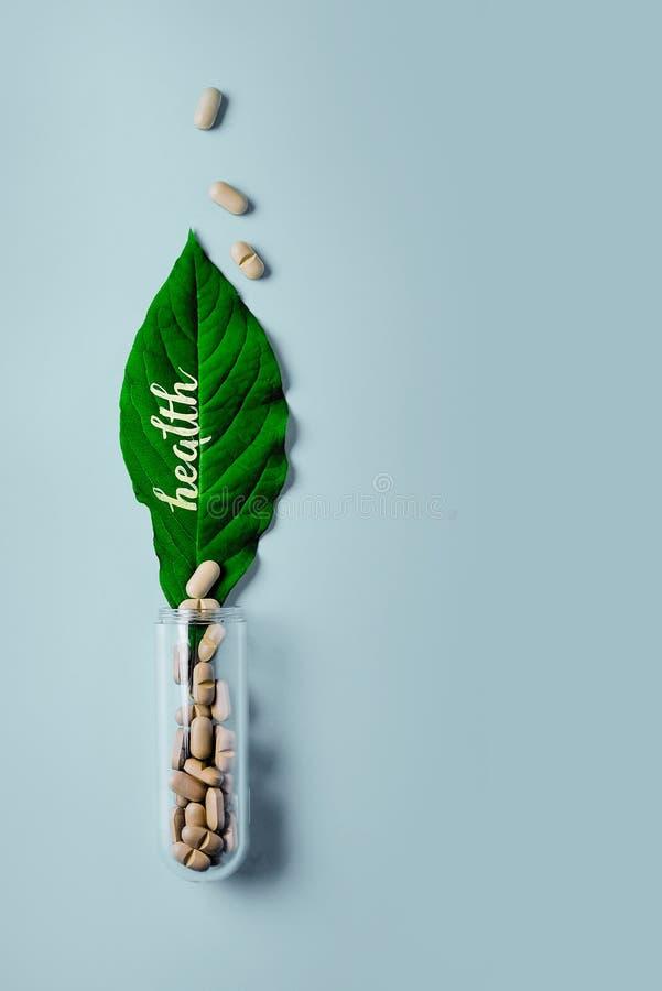 自然菜药片、添加剂、绿色叶子和瓶 心血管病的健康生活方式和预防 免版税图库摄影