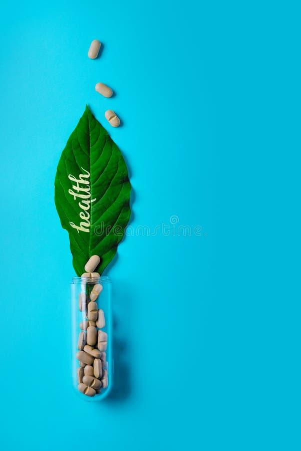自然菜药片、添加剂、绿色叶子和瓶 自然和植物健康的概念 健康生活方式 免版税图库摄影