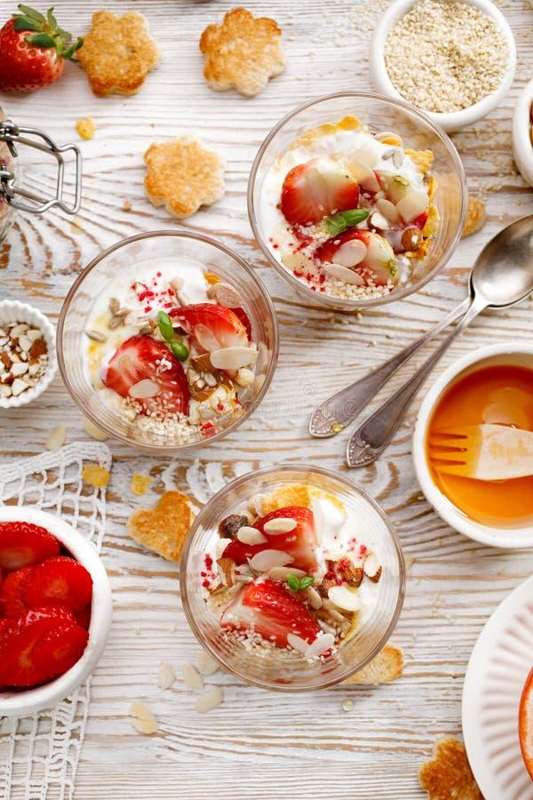 自然酸奶用新鲜的新鲜的草莓、格兰诺拉麦片、蜂蜜、坚果和种子在玻璃盘 可口早餐或点心 免版税库存图片