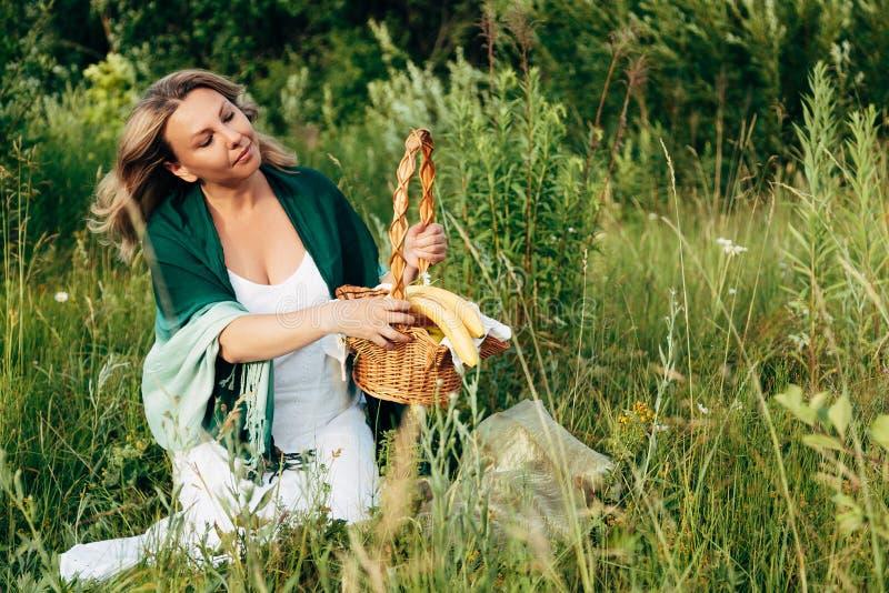 自然野餐篮子的美丽的白肤金发的女孩在软的日落的光芒 库存图片