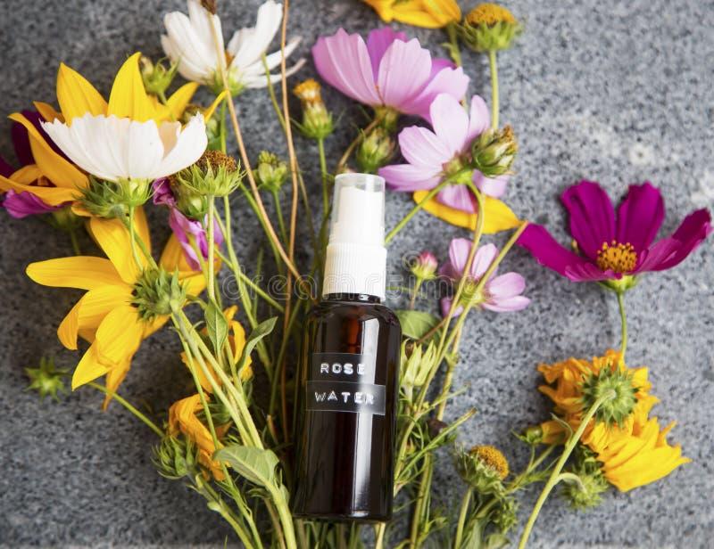 自然面孔调色剂奉承话瓶和花,有机skincar 库存图片